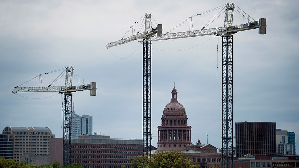 The Texas State Capitol building stands past construction cranes at the University of Texas at Austin campus in Austin, Texas, U.S., on Saturday, April 4, 2015. About 900,000 people live in the city of Austin and that number is expected to reach nearly 1.3 million by 2040, a 40 percent increase, according to city figures. More than 100 people move to the city a day, according to the city's demographer.