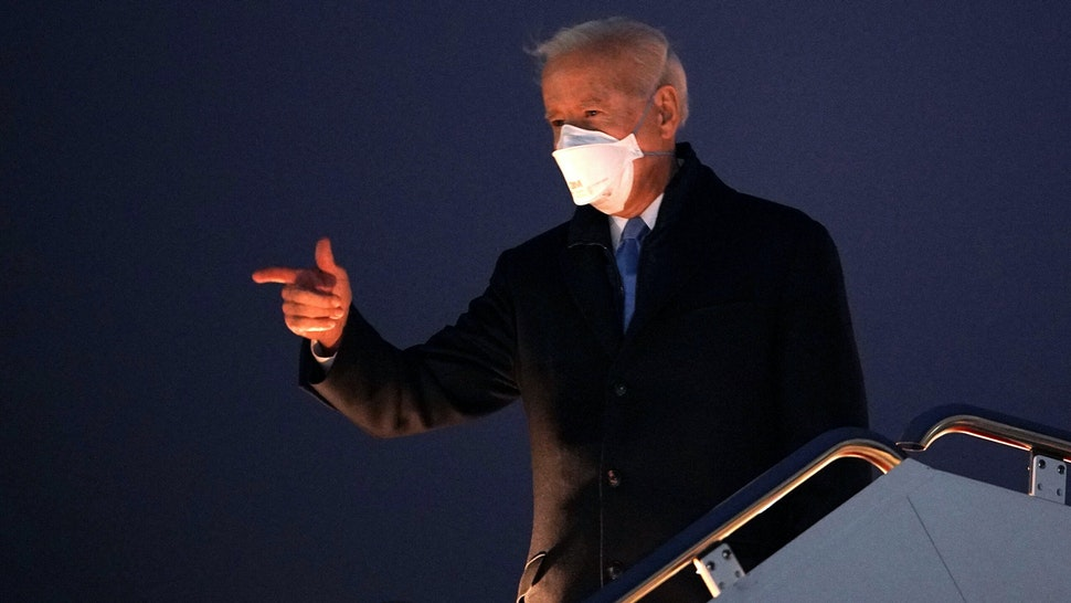 US President Joe Biden gestures as he boards Air Force One before departing from Andrews Air Force Base in Maryland on February 12, 2021. - Biden is heading the Camp David presidential retreat where he is due to spend the weekend.