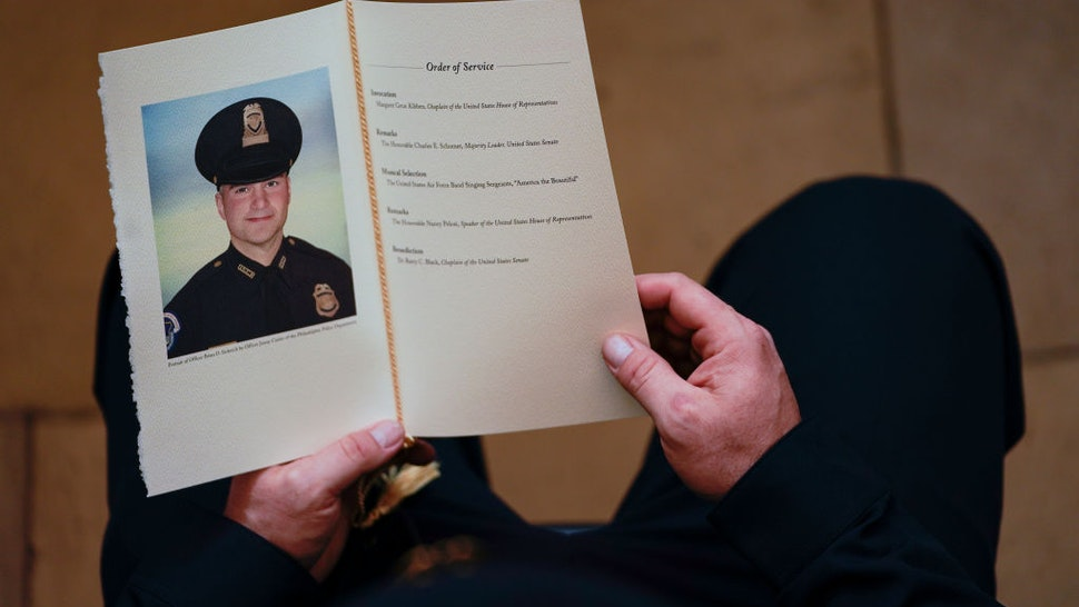 WASHINGTON, DC - FEBRUARY 3: A U.S. Capitol Police Officer holds a program for the ceremony memorializing U.S. Capitol Police Officer Brian D. Sicknick, 42, as he lies in honor in the Rotunda of the Capitol on February 3, 2021 in Washington DC. Officer Sicknick died as a result of injuries he sustained during the January 6 attack on the U.S. Capitol. He will lie in honor until February 3 and then be buried at Arlington National Cemetery.