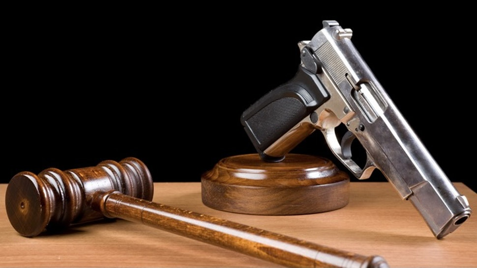 Wooden Gavel And Handgun On Table For Crime Punishment Concept - stock photo Wooden Gavel And Handgun On Table For Crime Punishment Concept.The background is black.The gun is placed on the right of frame while gavel is seen on the right side.The desk is brown wood.The photo was shot with a full frame DSLR camera in horizontal composition and in studio.Nobody is seen in photo.