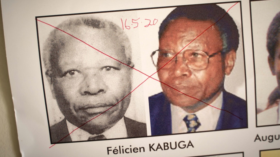 """The date of arrest and a red cross are seen written on the face of Felicien Kabuga, one of the last key suspects in the 1994 Rwandan genocide, on a wanted poster at the Genocide Fugitive Tracking Unit office in Kigali, Rwanda, on May 19, 2020. - French police on May 16, 2020 arrested one of the last key suspects in the 1994 Rwandan genocide, describing him as its """"financier"""" and one of the world's most wanted fugitives. Felicien Kabuga, once one of Rwanda's richest men, was living under a false identity in the Paris suburbs, the public prosecutor's office and police said in a joint statement."""