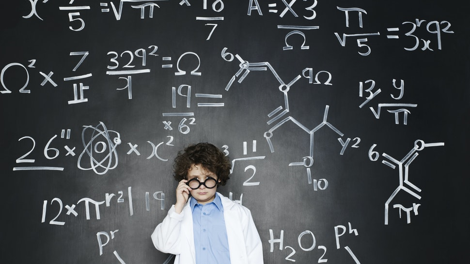 Boy as a professor with formulas behind him - stock photo