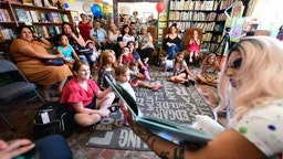 """Drag queen Scalene Onixxx reads to adults and children during Drag Queen Story Hour at Cellar Door Books in Riverside, California on June 22, 2019. - Athena and Scalene, their long blonde hair flowing down to their sequined leotards and rainbow dresses, are reading to around 15 children at a bookstore in Riverside. The scene would be unremarkable -- except that they are both drag queens. The reading workshop is part of """"Drag Queen Story Hour,"""" an initiative launched in 2015 by a handful of libraries and schools across the United States. (Photo by Frederic J. BROWN / AFP) (Photo credit should read FREDERIC J. BROWN/AFP via Getty Images)"""