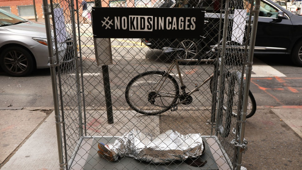A pop-up art installation depicting a small child curled up underneath a foil survival blanket in a chain-link cage stands along a Brooklyn street on June 12, 2019 in New York City.