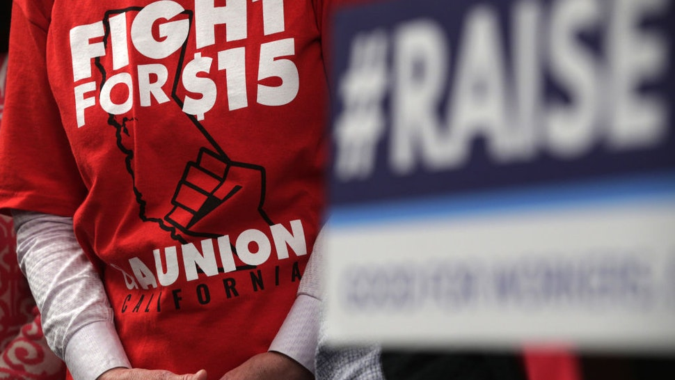 """WASHINGTON, DC - JULY 18: An activist wears a """"Fight For $15"""" T-shirt during a news conference prior to a vote on the Raise the Wage Act July 18, 2019 at the U.S. Capitol in Washington, DC. The legislation would raise the federal minimum wage from $7.25 to $15 by 2025. (Photo by Alex Wong/Getty Images)"""