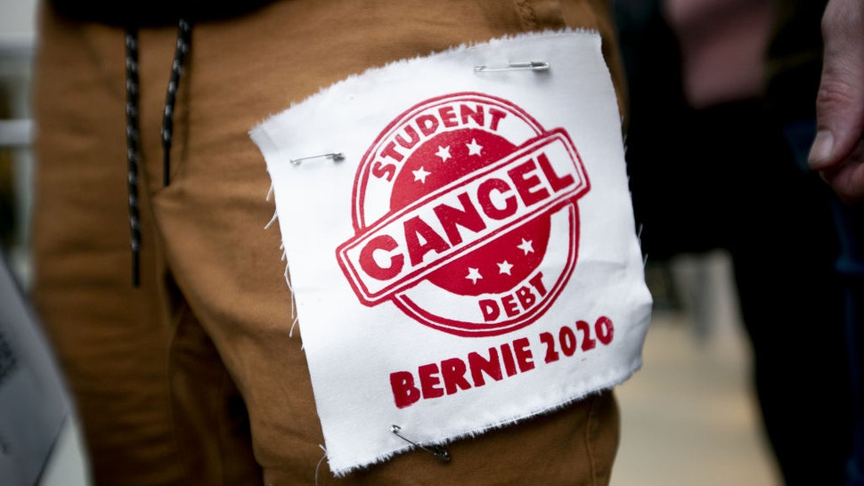 """An attendee wears a patch that reads """"Cancel Student Debt"""" ahead of a Get Out The Vote rally with Senator Bernie Sanders, an Independent from Vermont and 2020 presidential candidate, in Detroit, Michigan, U.S., on Friday, March 6, 2020. Sanders said his competitor, Joe Biden, could beat President Donald Trump in November, but added that he would be the stronger general-election candidate. Photographer: Anthony Lanzilote/Bloomberg via Getty Images"""