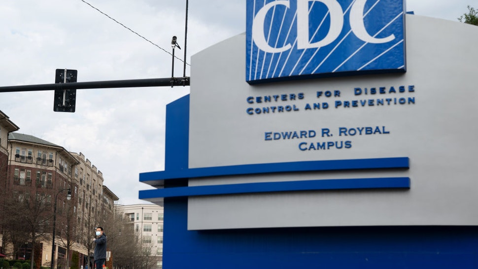 A pedestrian wearing a protective face mask walks past the Centers for Disease Control and Prevention (CDC) headquarters in Atlanta, Georgia, U.S, on Saturday, March 14, 2020.