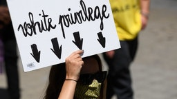"""A woman holds a placard reading """"White privilege"""" during a demonstration on June 14, 2020, in Barcelona, as part of the worldwide protests against racism and police brutality. - The protests are part of a worldwide movement following the killing in the United States of African-American man George Floyd who died after a white policeman knelt on his neck for several minutes. (Photo by Josep LAGO / AFP) (Photo by JOSEP LAGO/AFP via Getty Images)"""