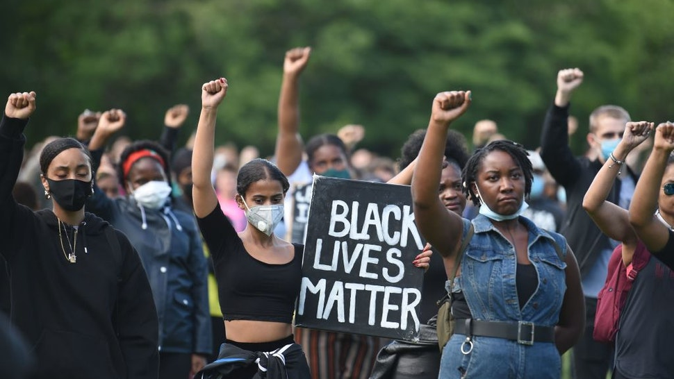 TOPSHOT - Protesters hold up fists at a gathering in support of the Black Lives Matter movement on Woodhouse Moor in Leeds in northern England on June 21, 2020, in the aftermath of the death of unarmed black man George Floyd in police custody in the US. (Photo by Oli SCARFF / AFP) (Photo by OLI SCARFF/AFP via Getty Images)