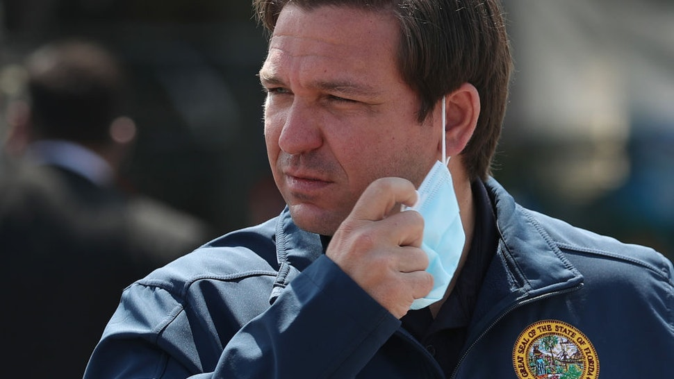 Florida Gov. Ron DeSantis takes his mask off as he prepares to speak during a press conference at the Hard Rock Stadium testing site on May 06, 2020 in Miami Gardens, Florida.