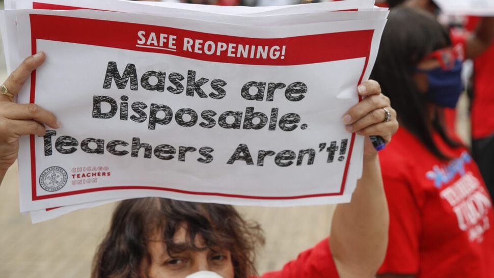 A woman holds a sign during the Occupy City Hall Protest and Car Caravan hosted by Chicago Teachers Union in Chicago, Illinois, on August 3, 2020. - Teachers and activists hold car caravan all over the country on August 3, 2020 to demand adequate classroom safety measures as schools debate reopening.