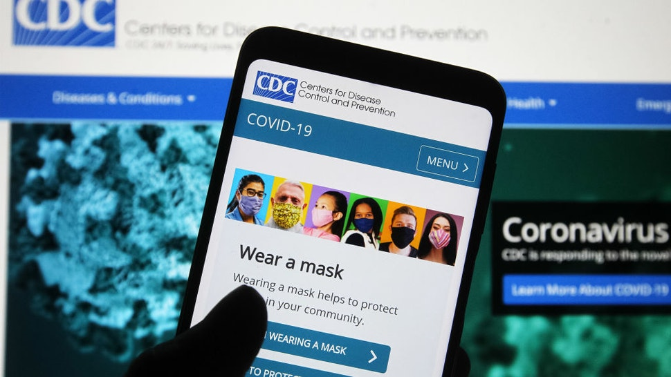UKRAINE - 2020/11/09: In this photo illustration Centers for Disease Control and Prevention (CDC) website with people wearing facemasks is seen displayed on a smartphone with a background of a computer screen. The Covid-19 global cases pass 50 million and 10 million in the U.S., according to internet online trackers of the coronavirus spread. (Photo Illustration by Pavlo Gonchar/SOPA Images/LightRocket via Getty Images)