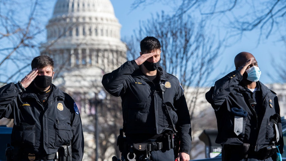 U.S. Capitol Police officers salute as a hearse carrying the body of Officer Brian D. Sicknick, who was killed by rioters Wednesday, passes members of the Capitol and Metropolitan police during a procession on Third Street on Sunday, January 10, 2021.