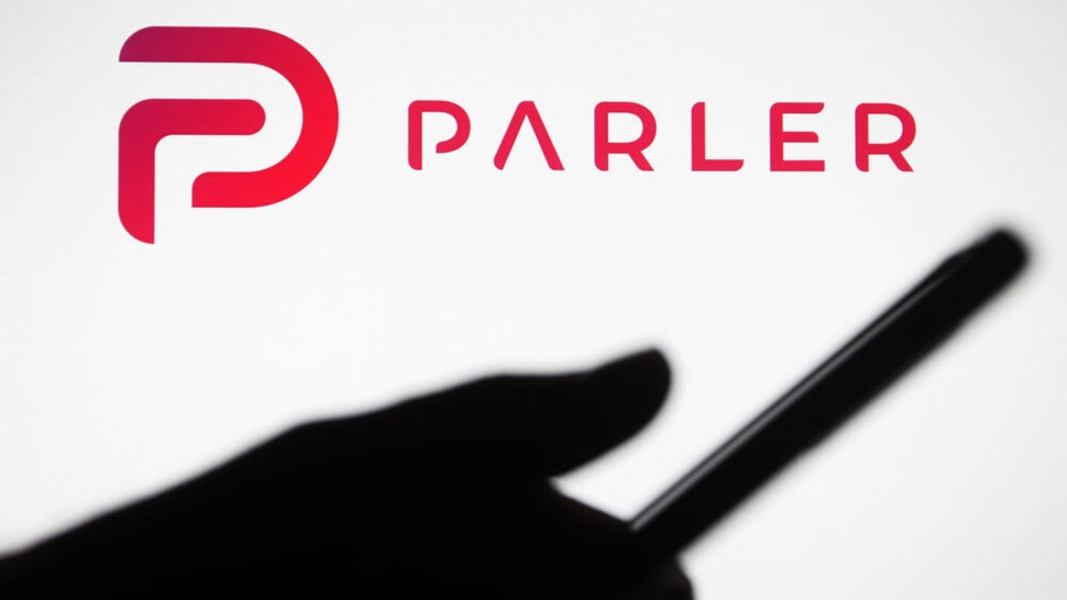 UKRAINE - 2021/01/10: In this photo illustration the Parler logo seen in front of a silhouette hand holding a smartphone. Google, Apple and Amazon have suspended the social networking app Parler. Parler became unavailable in App Store, Google Play and Amazon Web Services, reportedly as said insufficient control over user posts that encouraged violence, reportedly by media.