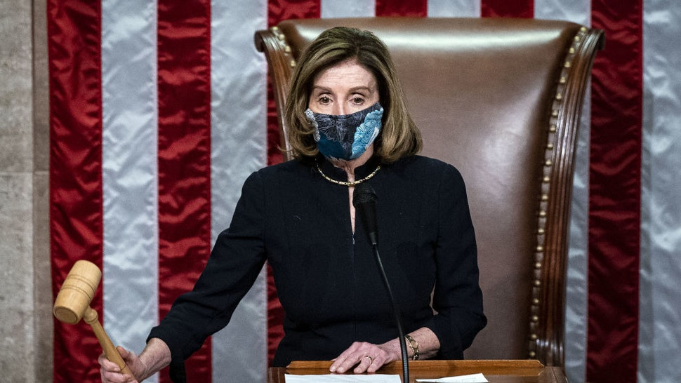U.S. House Speaker Nancy Pelosi, a Democrat from California, wears a protective mask while banging the Speaker's gavel on the floor of the House at the U.S. Capitol in Washington, D.C., U.S., on Wednesday, Jan. 13, 2021. President Donald Trump was impeached by the U.S. House on a single charge of incitement of insurrection for his role in a deadly riot by his supporters that left five dead and the Capitol ransacked, putting an indelible stain on his legacy with only a week left in his term. Photographer: Al Drago/Bloomberg via Getty Images