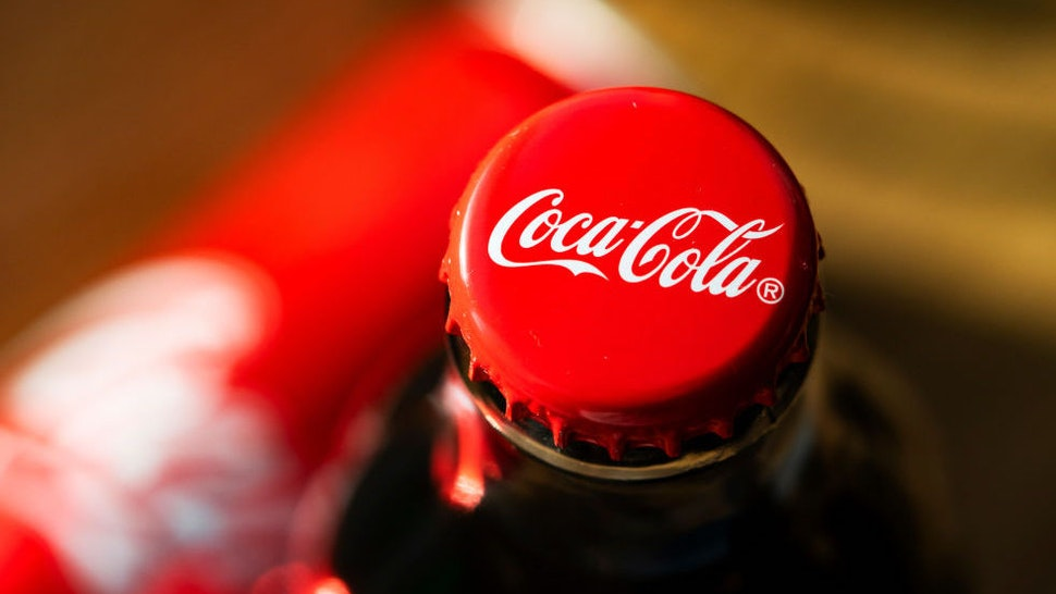 In this photo illustration a glass bottle of Coca-Cola seen displayed.
