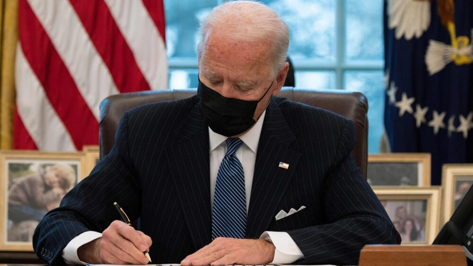 US President Joe Biden signs an Executive Order reversing Trump era ban on Transgender serving in the military while in the Oval Office of the White House in Washington, DC, on January 25, 2021.