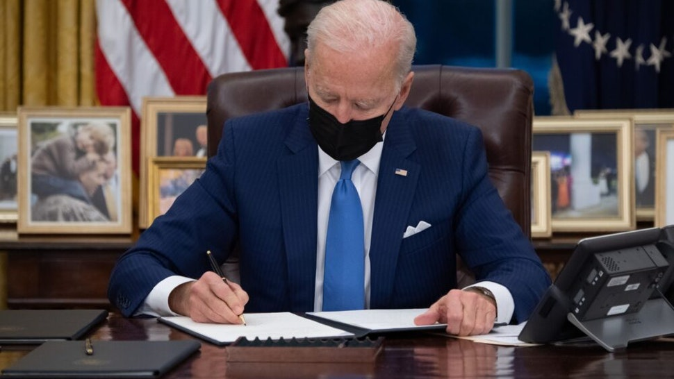 US President Joe Biden signs executive orders related to immigration in the Oval Office of the White House in Washington, DC, February 2, 2021.