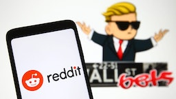 UKRAINE - 2021/02/08: In this photo illustration a Reddit logo is seen on a mobile phone screen in front of WallStreetBets (WSB) logo of a subreddit where participants discuss stock and options trading.