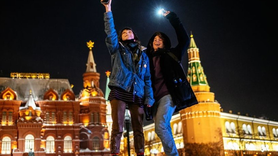 Young people turn on the flashlights of their mobile phones in support of jailed opposition politician Alexei Navalny near Red Square in Moscow on February 14, 2021. - The gathering came after authorities sentenced Navalny last week to nearly three years in prison and unleashed a crackdown on his supporters. Navalny's arrest on arrival back in Russia last month sparked nationwide protests that saw more than 10,000 people detained and led to allegations of police abuse. (Photo by Dimitar DILKOFF / AFP) (Photo by DIMITAR DILKOFF/AFP via Getty Images)