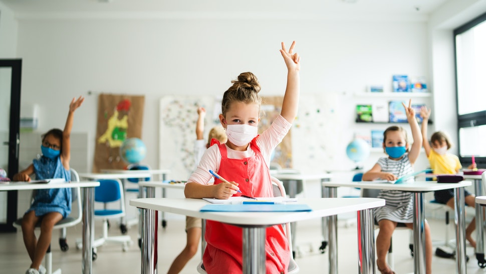 Small children with face mask back to school after coronavirus quarantine, learning. - stock photo