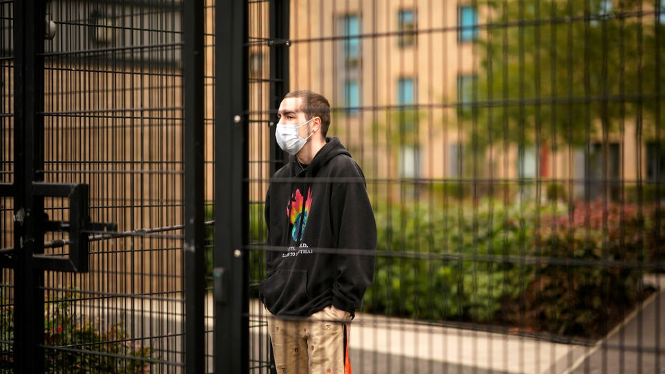MANCHESTER, ENGLAND - SEPTEMBER 28: Students who are self-isolating stand behind the security fencing of theoir accommodation as they are interviewed by a television crew on September 28, 2020 in Manchester, England. Around 1,700 students across two student housing blocks were told to self-isolate after more than 100 students recently tested positive for Covid-19. The students were told to self-isolate for 14 days even if they were not experiencing symptoms. (Photo by Christopher Furlong/Getty Images)