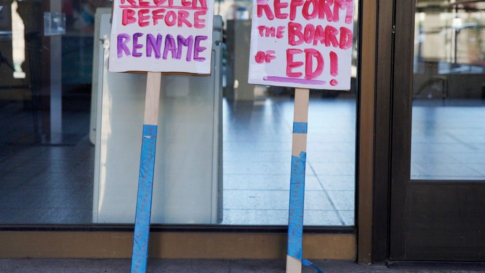 Protesters leave their signs outside the SFUSD building after a rally and march, Saturday, Feb. 6, 2021, in San Francisco, Calif.