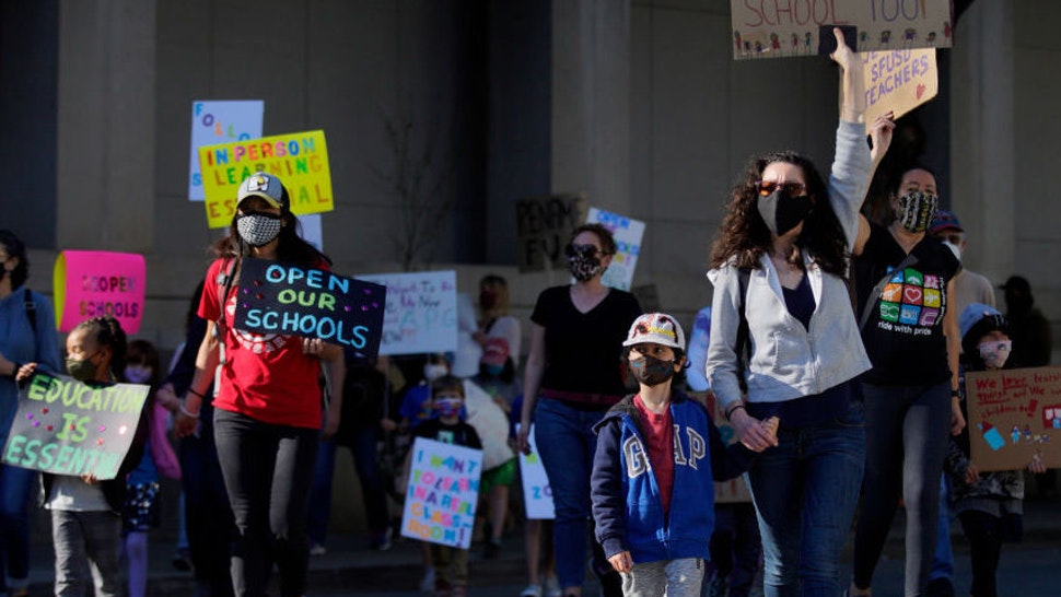 SAN FRANCISCO, CA - FEB. 6: Hundreds of people march to City Hall after rallying outside the SFUSD building, Saturday, Feb. 6, 2021, in San Francisco, Calif. People protested against remote education and demanded schools to reopen in-person education. (Santiago Mejia/The San Francisco Chronicle via Getty Images)