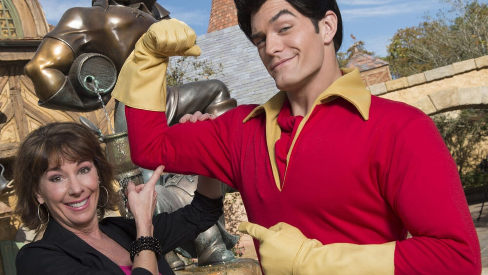 "LAKE BUENA VISTA, FL - DECEMBER 05: In this handout image provided by Disney Parks, Broadway and recording star Paige O'Hara poses with Disney's ""Beauty and the Beast"" character Gaston in New Fantasyland December 5, 2012 at the Magic Kingdom park at Walt Disney World in Lake Buena Vista, Florida. The new land, which holds its official Grand Opening tomorrow, features several settings and scenes from Disney's ""Beauty and the Beast,"" including Gaston's Tavern. O'Hara, who was honored as a ""Disney Legend"" in 2011, provided the singing and speaking voice for Belle, the animated star of ""Beauty and the Beast."""