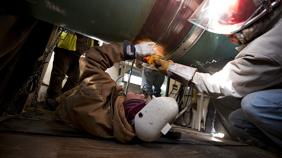 Workers inspect a weld on the joint between two sections of pipe on a Gulf Coast Project pipeline in Atoka, Oklahoma, U.S., on Monday, March 11, 2013.