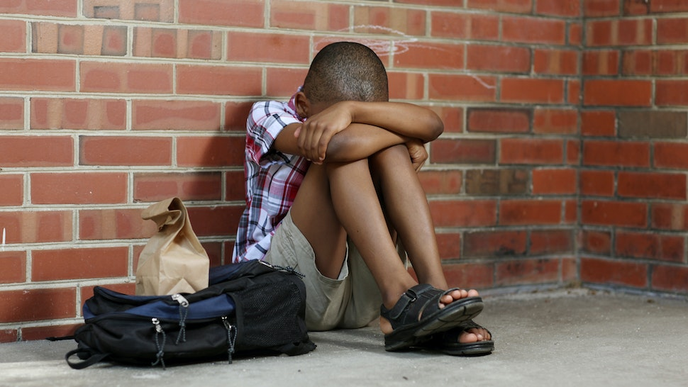 Sitting alone a poor child is bullied at school. - stock photo