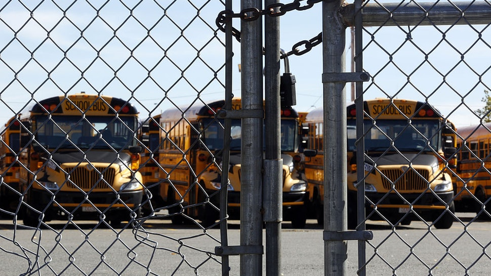 Buses are seen behind a padlocked gate after bus drivers were locked out of the yard in Dorchester, Mass., Oct. 8, 2013.