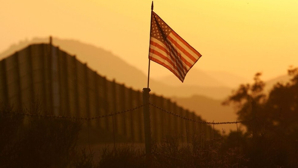 CAMPO, CA - OCTOBER 08: A U.S. flag put up by activists who oppose illegal immigration flies near the US-Mexico border fence in an area where they search for border crossers October 8, 2006 near Campo, California. The activists want the fence expanded into a fully-lit double-fenced barrier between the US (R) and Mexico. US Fish and Wildlife Service wardens and environmentalists warn that a proposed plan by US lawmakers to construct 700 miles of double fencing along the 2,000-mile US-Mexico border, in an attempt to wall-out illegal immigrants, would also harm rare wildlife. Wildlife experts say cactus-pollinating insects would fly around fence lights, birds that migrate by starlight in the desert wilderness would be confused, and large mammals such as jaguars, Mexican wolves, Sonoran pronghorn antelope, and desert bighorn sheep would be blocked from migrating across the international border, from California to Texas.