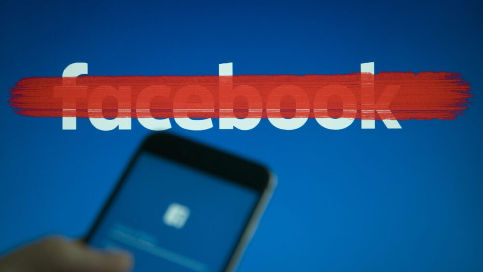 An iphone with a facebook login screen is seen with a striked out facebook logo in the background in this photo illustration on September 22, 2017.