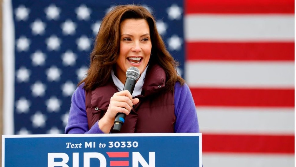 """Michigan Governor Gretchen Whitmer talks with people as Democratic vice presidential nominee Senator Kamala Harris (D-CA) takes part in a campaign stop at IBEW Local 58 on October 25, 2020 in Detroit, Michigan. - As she speaks to cheering crowds, drops in to neighborhood coffee shops or pays """"surprise"""" visits to college students, 56-year-old Kamala Harris has brought a jolt of youthful energy to the low-key presidential campaign of her 77-year-old running mate, Democrat Joe Biden. (Photo by JEFF KOWALSKY / AFP) (Photo by JEFF KOWALSKY/AFP via Getty Images)"""