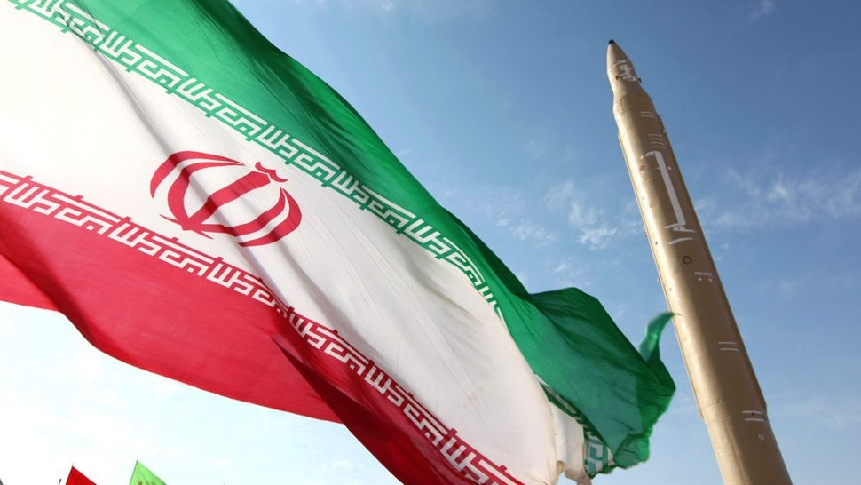 A picture taken on August 20, 2010 shows an Iranian flag fluttering at an undisclosed location in the Islamic republic next to a surface-to-surface Qiam-1 (Rising) missile which was test fired a day before Iran was due to launch its Russian-built first nuclear power plant. Iranian Defence Minister Ahmad Vahidi said the missile was entirely designed and built domestically and powered by liquid fuel.