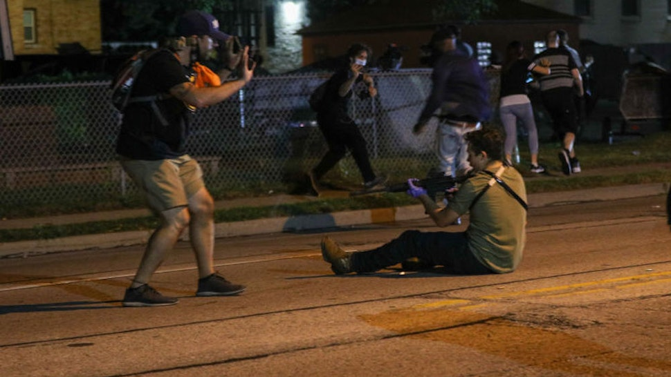 KENOSHA, WISCONSIN, USA - AUGUST 25: (EDITORS NOTE: Image contains graphic content.) A man (R) was shot in the chest as clashes between protesters and armed civilians who protect the streets of Kenosha against the arson during the third day of protests over the shooting of a black man Jacob Blake by police officer in Wisconsin, United States on August 25, 2020. (Photo by Tayfun Coskun/Anadolu Agency via Getty Images)