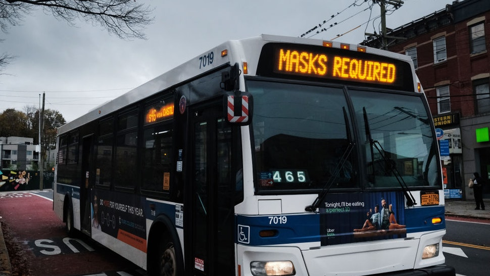 """NEW YORK, NEW YORK - NOVEMBER 12: A bus displays a message noting masks are required to board on November 12, 2020 in the in Staten Island borough of New York City. Staten Island's seven-day positive test rate for Covid-19 is the highest in the city. Two Staten Island ZIP codes have now risen above the five percent infection rate, prompting Gov. Andrew Cuomo to declare the borough a """"yellow zone,"""" which includes limits on outdoor gatherings to 25 people and attendance at churches to 50 percent capacity."""