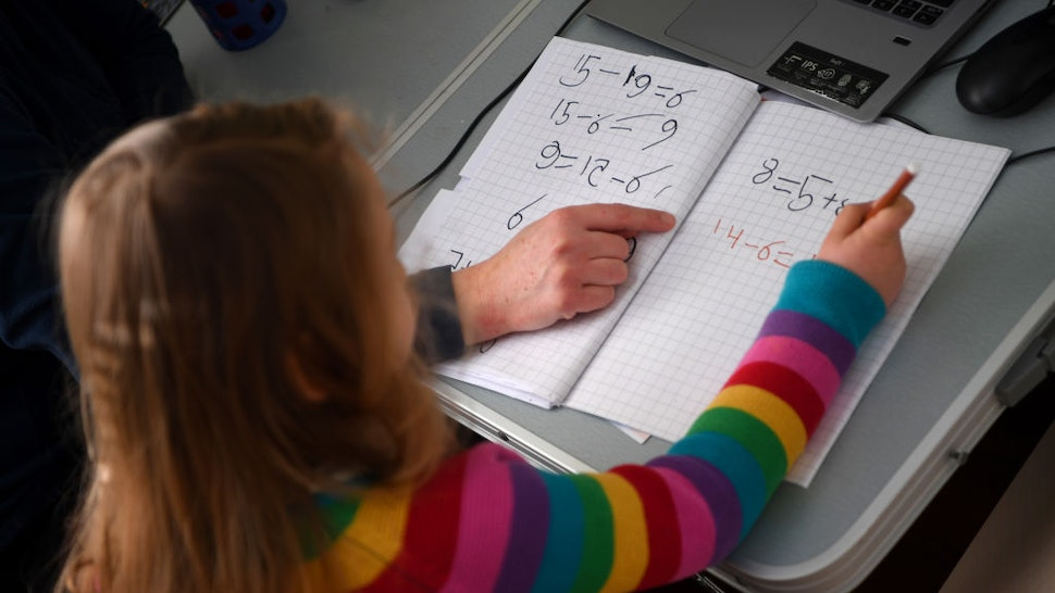 Five-year-old Lois Copley-Jones, who is the photographer's daughter, does her Maths studies in her bedroom on January 25, 2021 in Newcastle-under-Lyme, England. Under current government policy, schools in England wouldn't open before the February half-term break at the earliest, but the Prime Minister has declined to commit to reopening them before Easter.