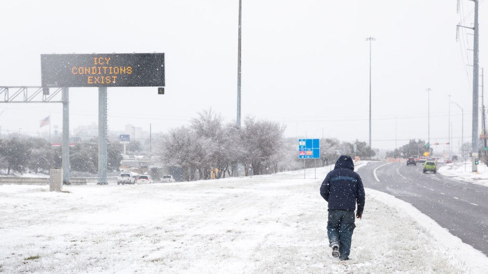 A pedestrians walks past a road sign warning commuters of icy conditions on a road in Austin, Texas, U.S., on Thursday, Feb. 18, 2021. Texas is restricting the flow of natural gas across state lines in an extraordinary move that some are calling a violation of the U.S. Constitutions commerce clause.