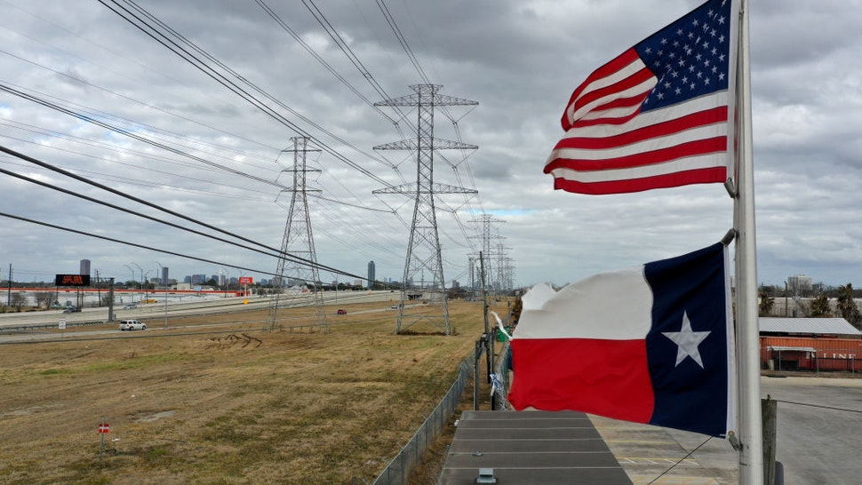 HOUSTON, TEXAS - FEBRUARY 21: The U.S. and Texas flags fly in front of high voltage transmission towers on February 21, 2021 in Houston, Texas. Millions of Texans lost power when winter storm Uri hit the state and knocked out coal, natural gas and nuclear plants that were unprepared for the freezing temperatures brought on by the storm. Wind turbines that provide an estimated 24 percent of energy to the state became inoperable when they froze.