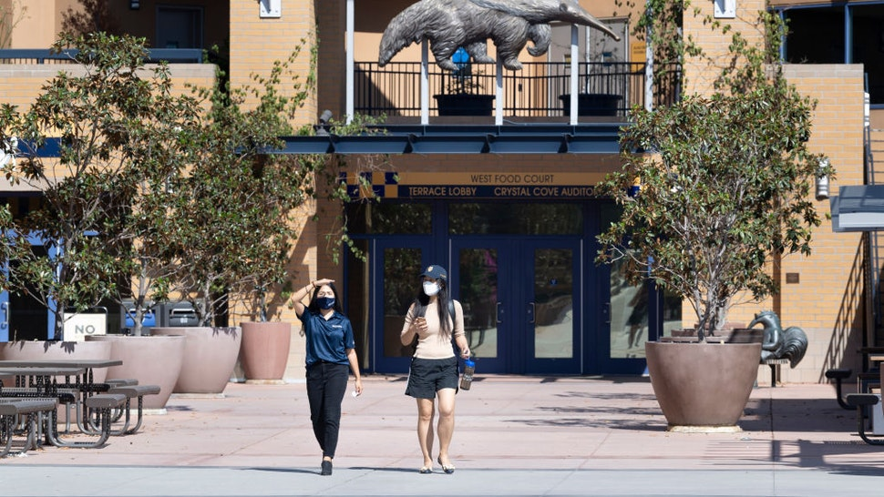 """Two women walk through a mostly empty campus at the University of California, Irvine in Irvine, CA on Friday, October 2, 2020. Classes started Thursday, October 1st but most are online, leaving few students on campus. """"nStudent housing was at 43% capacity, or about 6,600 students, and most classes were online due to COVID-19 restrictions. Fall quarter is almost entirely online with a few undergraduate classes in-person."""