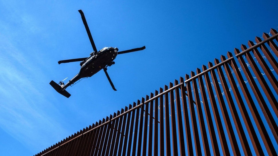 A US border patrol helicopter overflies the US-Mexico border fence as US President Donald Trump visits Calexico, California, as seen from Mexicali, Baja California state, Mexico, on April 5, 2019. - President Donald Trump flew Friday to visit newly built fencing on the Mexican border, even as he retreated from a threat to shut the frontier over what he says is an out-of-control influx of migrants and drugs.