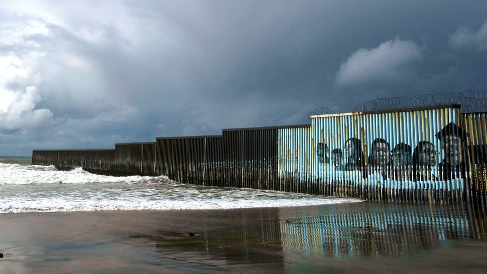 TOPSHOT - Waves crash on the US-Mexico border fence as winter storm clouds are seen over Playas de Tijuana, Baja California state, Mexico, on January 29, 2021. - A winter storm is expected to hit northwestern Mexico.