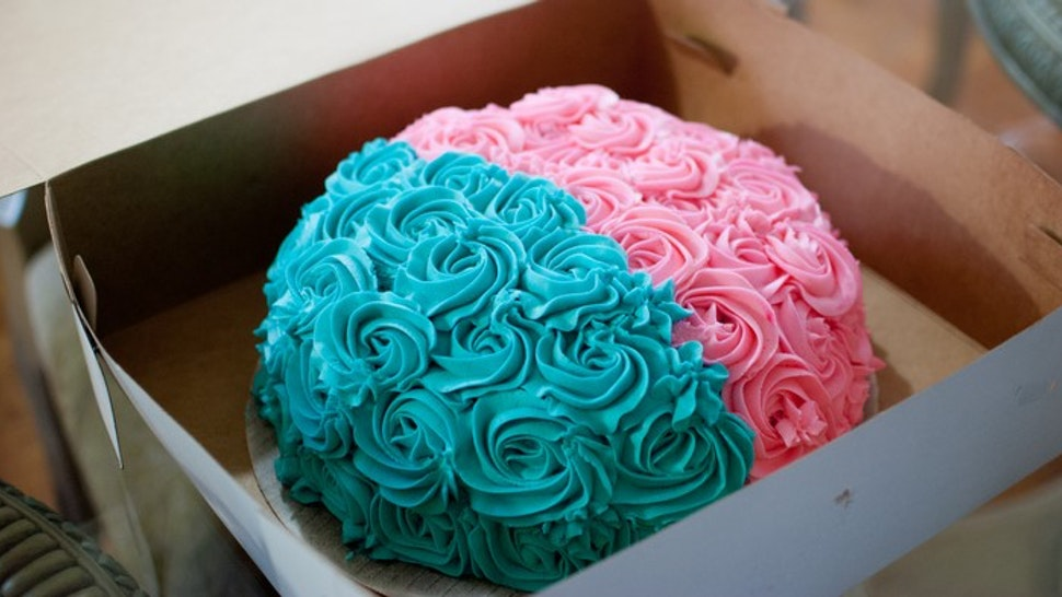 A pink and blue cake used at a gender reveal baby shower.