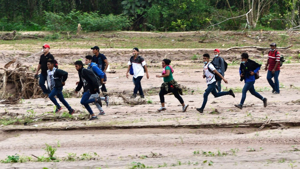 Migrants heading to the border with Guatemala on their way to the United States, cross the dried riverbed of the Copan River in the municipality of Santa Rita, in the Honduran department of Copan, on January 15, 2021. - Hundreds of asylum seekers are forming new migrant caravans in Honduras, planning to walk thousands of kilometers through Central America to the United States via Guatemala and Mexico, in search of a better life under the new administration of President-elect Joe Biden.