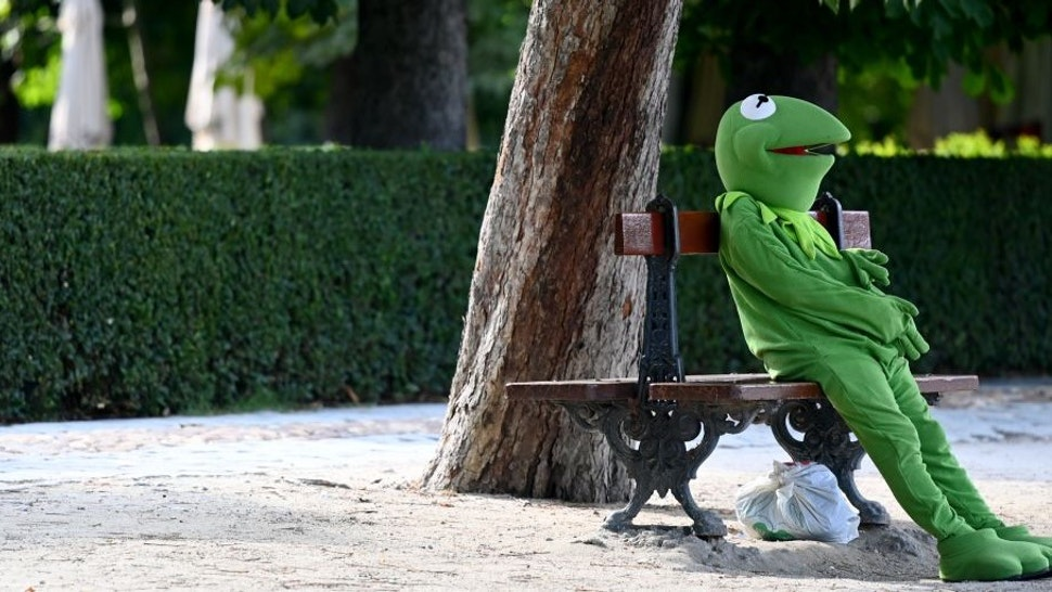 A man dressed as the Muppets show character Kermit the Frog waits for a tip at the Retiro Park in Madrid, on July 01, 2020. (Photo by Gabriel BOUYS / AFP) (Photo by