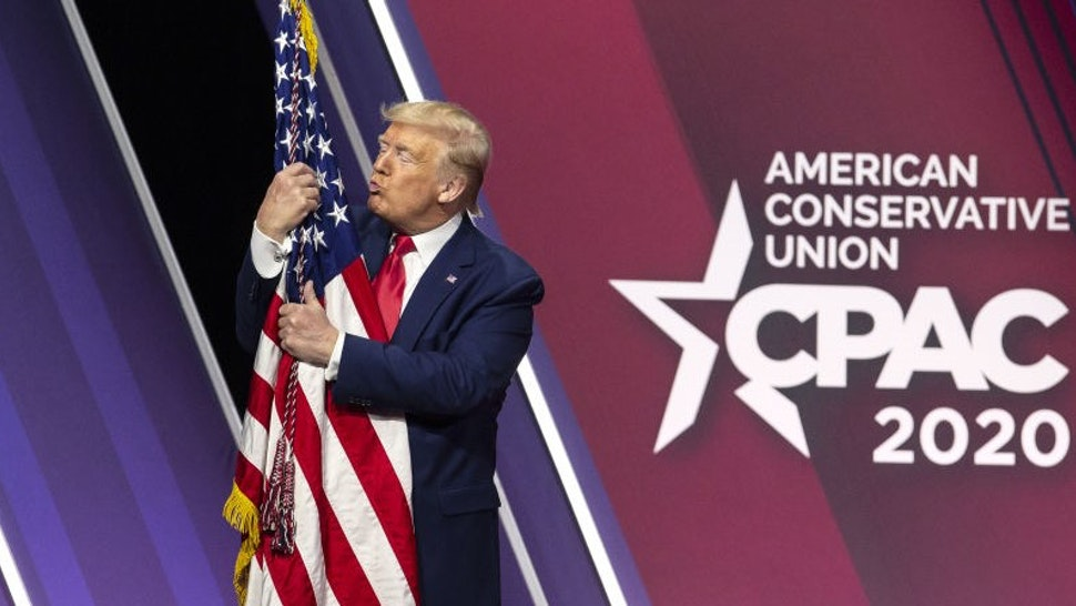 U.S. President Donald Trump hugs and kisses the American flag during the Conservative Political Action Conference (CPAC) in National Harbor, Maryland, U.S., on Saturday, Feb. 29, 2020. At a White House press conference on Saturday, Trump said he was confident in the U.S. stock market, after a week that saw the biggest loss in the S&P 500 index since 2008. Photographer: