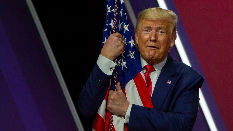 NATIONAL HARBOR, MARYLAND - FEBRUARY 29: US President Donald Trump hugs the flag at the annual Conservative Political Action Conference (CPAC) at Gaylord National Resort & Convention Center February 29, 2020 in National Harbor, Maryland. Conservatives gather at the annual event to discuss their agenda. (Photo by