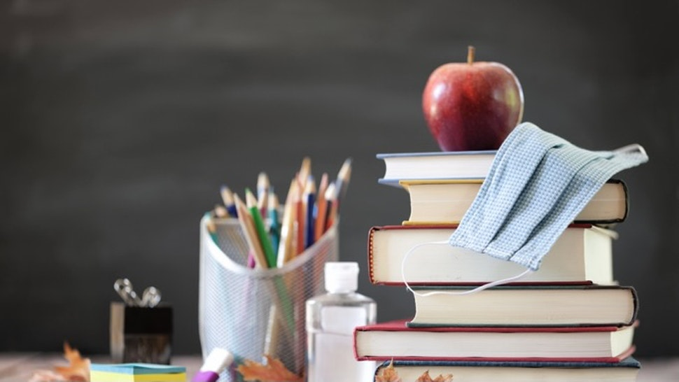 Back to School with Face Mask - stock photo Back to School. Stack of Books with Apple on Top and protective face mask